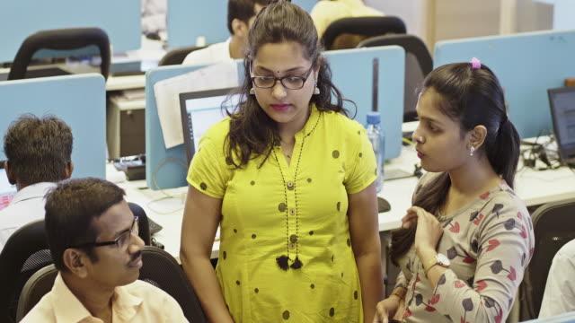 vidéos et rushes de une femme gestionnaire de bureau forme de nouveaux employés au sujet de leur système de crm - peuple du sous continent indien