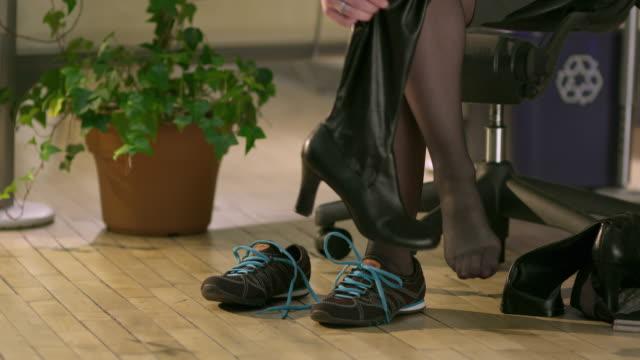 cu female office worker changing shoes in office, appleton, wisconsin, usa - ウィスコンシン州アップルトン点の映像素材/bロール