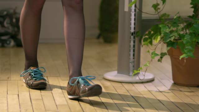 cu pan female office worker sitting down taking shoes off in office, appleton, wisconsin, usa - ウィスコンシン州アップルトン点の映像素材/bロール