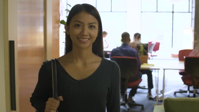 Female office worker standing and smiling at camera.
