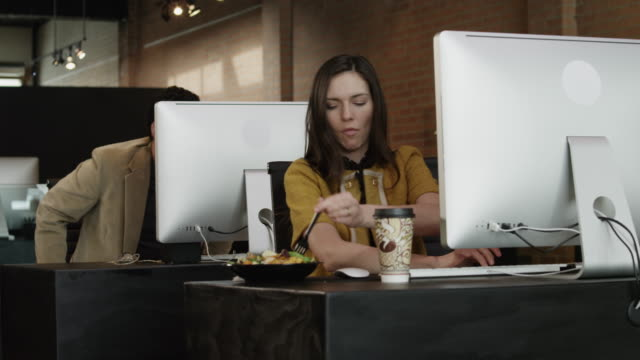 vidéos et rushes de ms ds female office worker using computer and eating at office desk / provo,utah,usa - surchargé de travail
