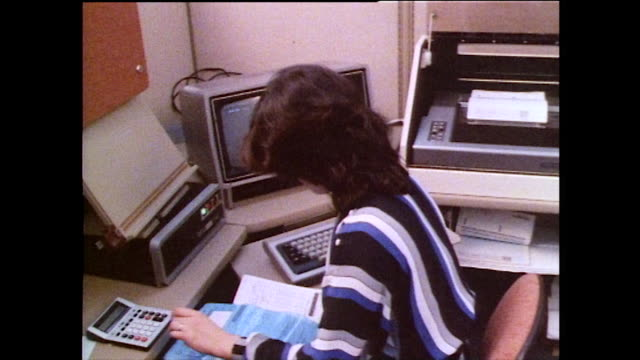 female office workers at desks with old computers; 1985 - 電卓点の映像素材/bロール