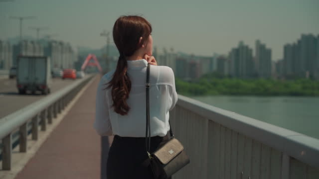 a female office worker's back looks on the bridge - south korea stock videos and b-roll footage
