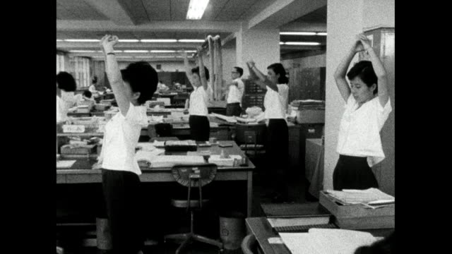 female office workers exercise together at desk; 1966 - bbc archive stock-videos und b-roll-filmmaterial