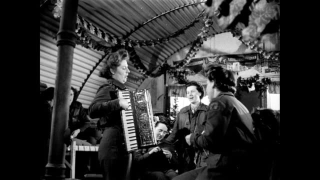 zi female officers singing christmas carols while playing an accordion in a decorated army bunker / united kingdom - 賛美歌点の映像素材/bロール