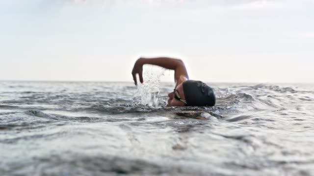 female open water swimmer swimming front crawl in the sea - swimming cap stock videos & royalty-free footage