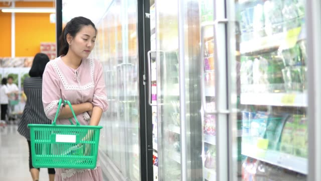 female opens freezer door and puts frozen vegetables into his shopping - dairy product stock videos & royalty-free footage