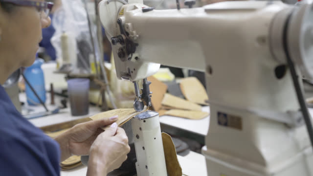 female operators using a sewing machine sewing shoe parts together - macchina per cucire video stock e b–roll