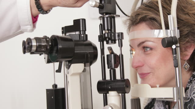 female ophthalmologist examining eye of  women - ophthalmologist stock videos and b-roll footage