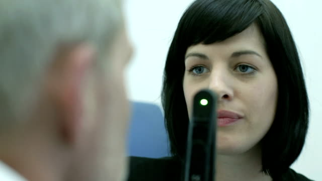 CU Female Optician examines Male patient with Ophthalmoscope.