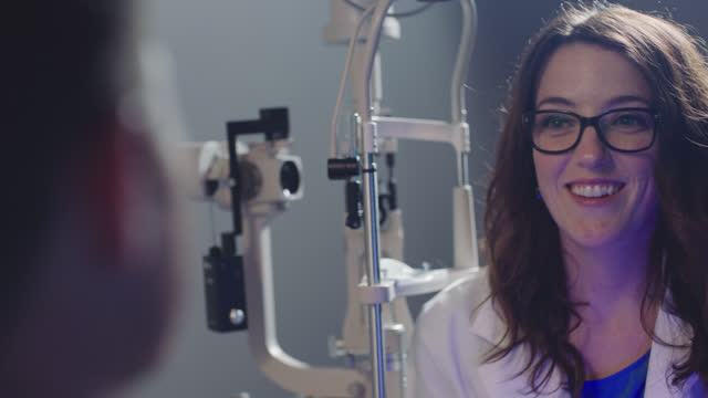 stockvideo's en b-roll-footage met ms ots. female optometrist chats with patient and smiles during eye exam. - opticien