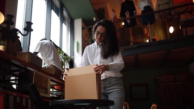 weibliche besitzerin eines bekleidungsgeschäfts, die sachen für die lieferung vorbereitet - 40 seconds or greater stock-videos und b-roll-filmmaterial