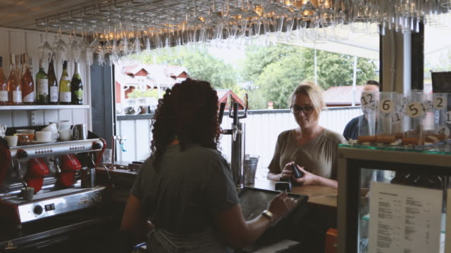 vídeos de stock, filmes e b-roll de female owner receiving payment and taking order from customers at restaurant - gastando dinheiro
