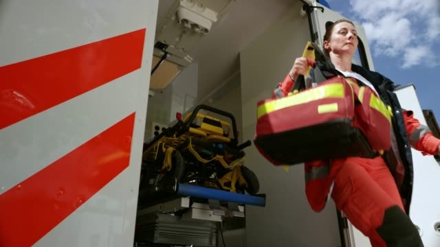 slo mo ds female paramedic rushing out of the ambulance vehicle with her bag - paramedic stock videos & royalty-free footage