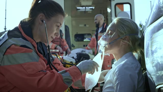Female paramedic talking to the injured woman sitting on the ground at the scene of a car accident and breathing with the oxygen mask