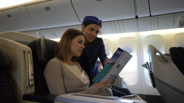 female passenger asking friendly air stewardess something while pointing at a magazine - crew stock videos & royalty-free footage
