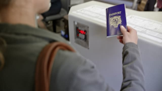 Female passenger handing her passport to the female employee at the check in desk