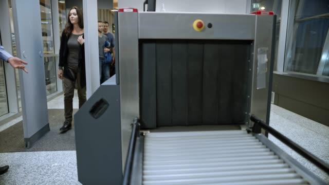 ds female passenger walking through the metal detector at the airport security - sicurezza sul posto di lavoro video stock e b–roll