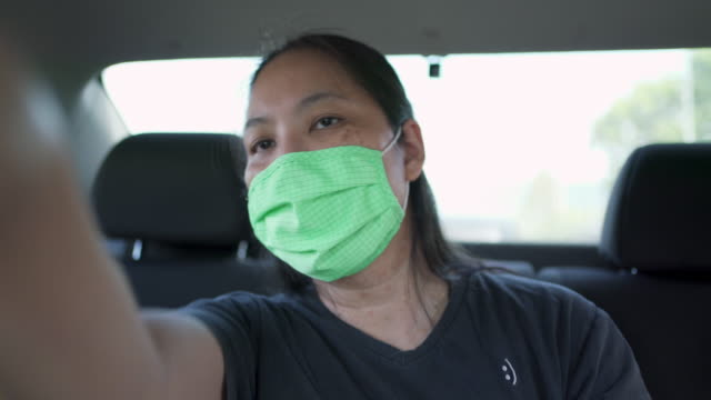 female passenger wearing mask on the taxi telling driver about the way to go - brown stock videos & royalty-free footage