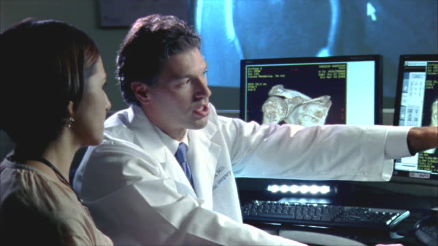 CU, Female patient and doctor showing shoulder 3D scan on computer monitor, Swedish American Heart Hospital, Rockford, Illinois, USA