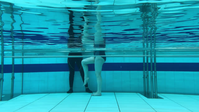 female patient exercising her legs next to physiotherapist during hydrotherapy - hydrotherapy stock videos & royalty-free footage
