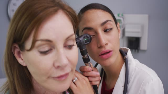 female patient having her ear examined with otoscope by young latina doctor - medical instrument stock videos and b-roll footage