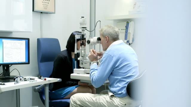 ms female patient is examined by the male optician. - optical equipment stock videos & royalty-free footage