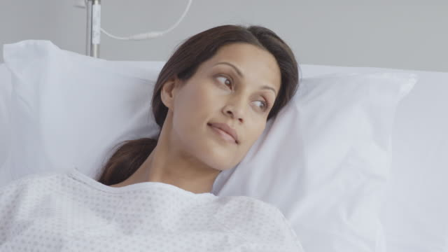 female patient looking away while lying in bed - examination gown stock videos and b-roll footage