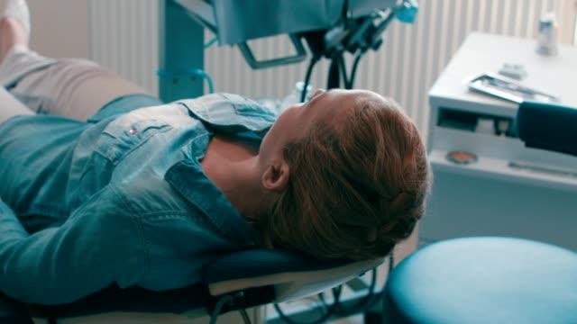 weibliche patienten liegen im zahnarztstuhl - über die schulter stock-videos und b-roll-filmmaterial