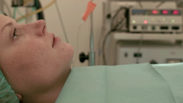 female patient lying on operating table - operating room stock videos and b-roll footage