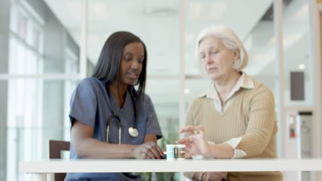 vídeos de stock e filmes b-roll de female patient with diabetes being helped by nurse - baixo