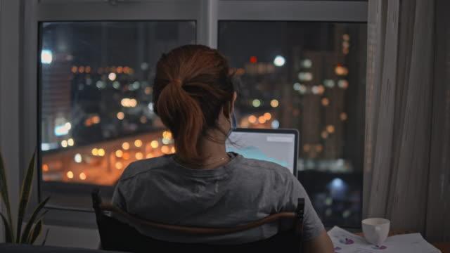 le pazienti detenute in casa usano il laptop per lavorare nella stanza di notte - vista posteriore video stock e b–roll