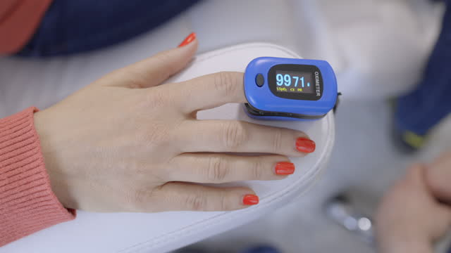 female patient's hand with blood saturation measuring instrument - oximeter - index finger stock videos & royalty-free footage