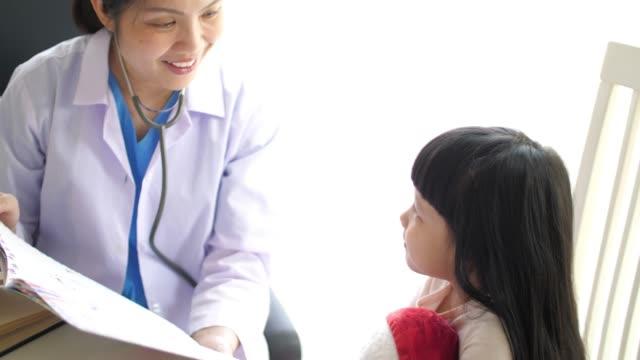 女性小児科医医師が聴診器、スローモーションで子供の女の子を調べる - 女医点の映像素材/bロール