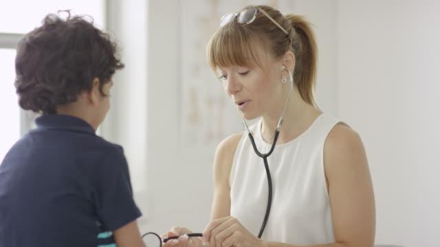 female pediatrician with patient - misurare il polso video stock e b–roll