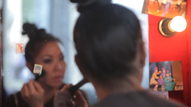 female performer putting make up on - メイクアップブラシ点の映像素材/bロール