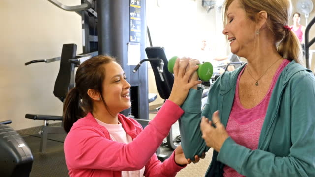 Female personal trainer or physical therapist works with senior client