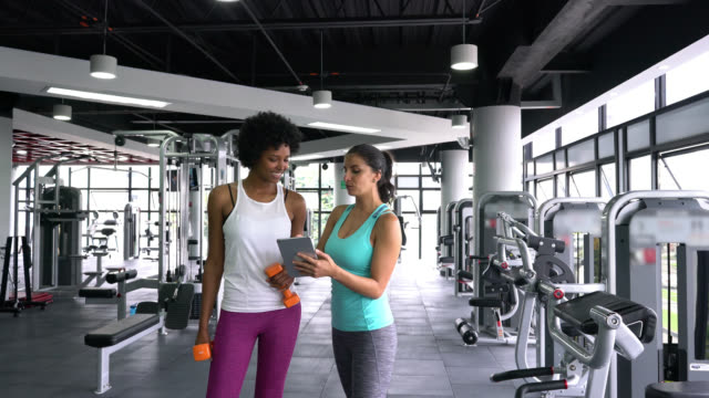 female personal trainer showing black young customer her workout on tablet while talking - coach stock videos & royalty-free footage