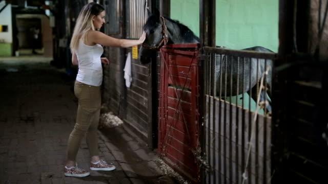 Kvinnliga petting häst i stall