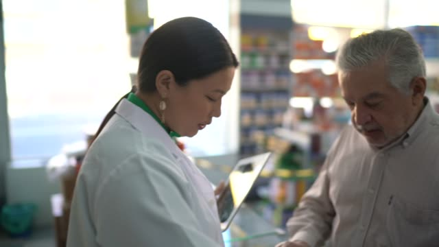 female pharmacist giving medications to senior customer - chemist stock videos & royalty-free footage