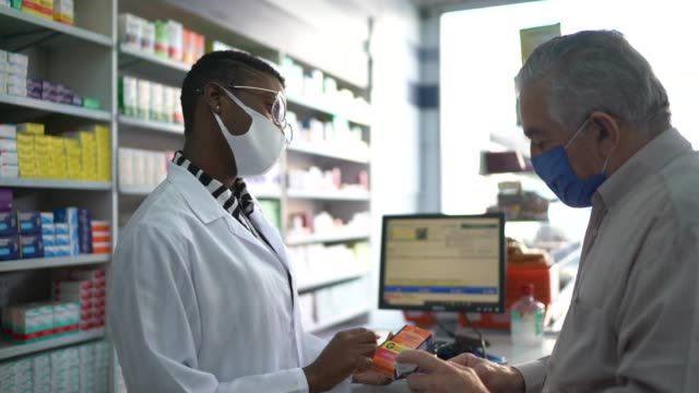 female pharmacist giving medications to senior customer - pharmacist stock videos & royalty-free footage
