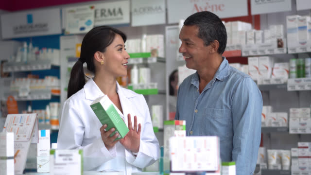 Female pharmacist helping a client with a product