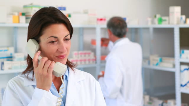 Female pharmacist phoning