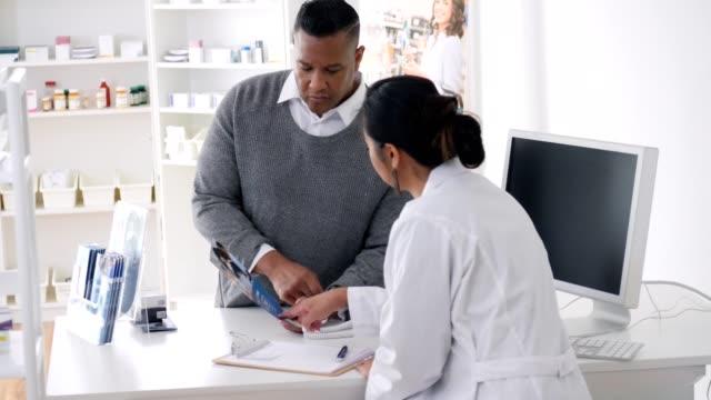 female pharmacist reviews pharmacy brochure with male customer - brochure stock videos & royalty-free footage