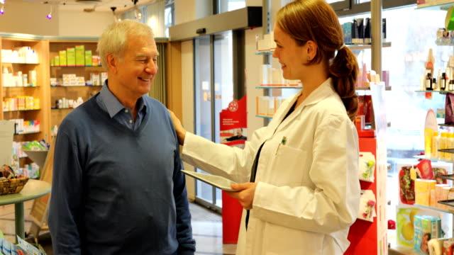 Female Pharmacist Talking To Senior Man In Store