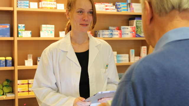 female pharmacist talking to senior man in store - prescription stock videos and b-roll footage