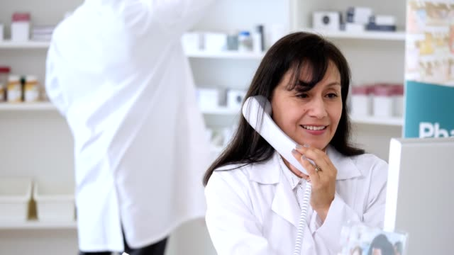 female pharmacist talks with customer on the phone - concept stock videos & royalty-free footage