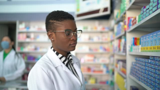 female pharmacist walking using digital tablet at pharmacy - pharmacist stock videos & royalty-free footage