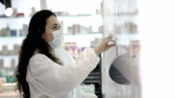 Female pharmacist wearing a surgical mask prepares the patient's medication