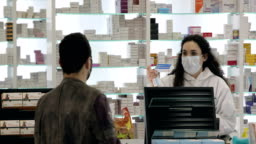 Female pharmacist wearing a surgical mask tells the male patient who wears a surgical mask how to use his medicine